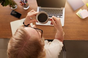 Woman drinking coffee at her desk.