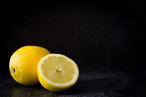 Lemons on black stone background
