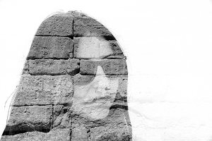 Woman and detail of old brick wall.