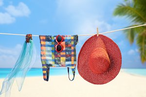 Beach outfit. Summer clothes set on tropical sea