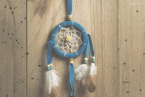 the dreamcatcher on wood background with sunlight, vintage filtered Images