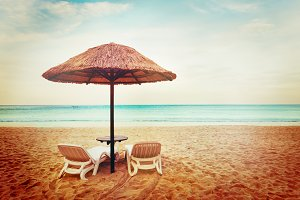 Two beach chairs with sun umbrellas