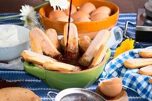 Cooking tiramisu dessert with espresso coffee and biscuits