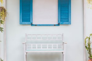 White bench and window on the porch.