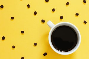 Top view of black coffee on yellow