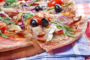 Pizza with dry cured ham and salad