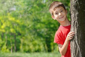Cute boy standing near tree