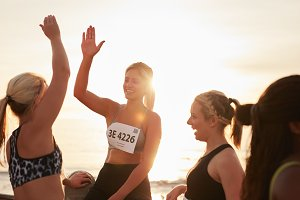Female runners high fiving
