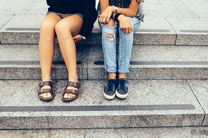 Two girls sitting in the city