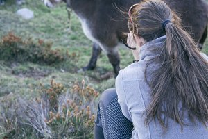Woman photographing a donkey