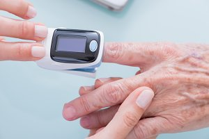 Doctor using finger pulse oximeter