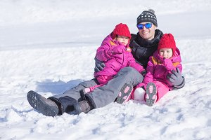 Father and little daughters at snow