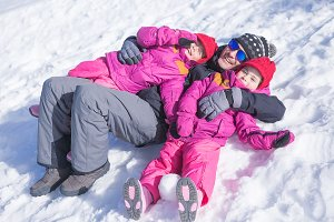 Father and two daughters on snow