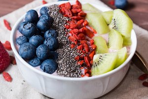 Smoothie bowl with strawberry smoothie, berries, kiwi and chia
