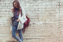 Young street fashion girl on the background of old brick wall. Outdoors, lifestyle.