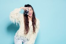 fashion stylish woman dancing and making photo using retro camera. Portrait on blue background in white sweater
