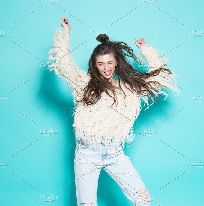 portrait of cheerful fashion hipster girl going crazy making funny face and dancing. Blue color background. - People