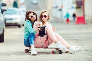 Hipster girlfriends taking a selfie in urban city context - Concept of friendship and fun with new trends and technology - Best friends eternalizing the moment with camera