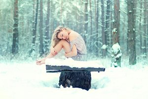 girl sitting on the snow in dress