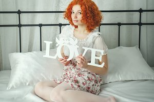 Red-haired girl in bedroom