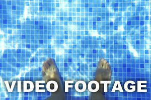 Male feet in clear water of the pool