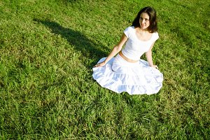 Girl in white dress in green grass