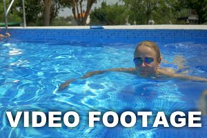 Smiling Woman Swimming in Home Pool