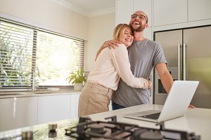 Loving couple with laptop in kitchen