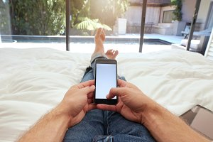 Man relaxing on bed using mobile