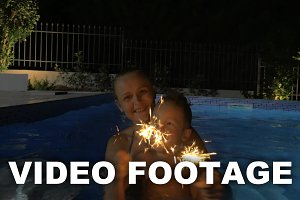Woman and Boy with Sparklers in Pool