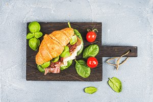 Croissant sandwich with smoked meat Prosciutto di Parma, sun dried tomatoes, fresh spinach and basil on dark wooden board over stone textured grey background
