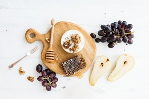 Camembert cheese with grape, walnuts, pear and honey on oak serving board