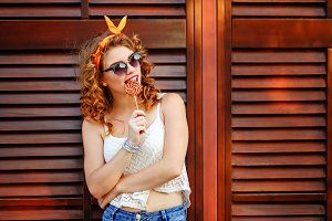 PinUp girl in sunglasses. Lollipop
