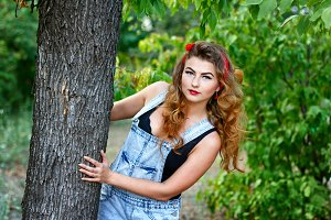 Pin-up girl hiding behind a tree