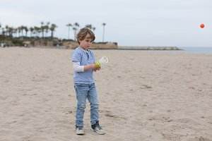Boy playing catcher ball on beach