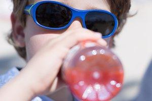 Boy drinking a tomato juice bottle