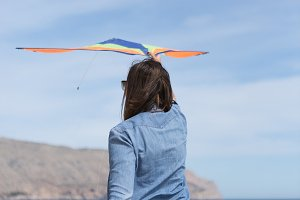 Woman with kite on the beach