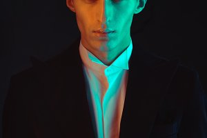Handsome man color face in suit  on black background