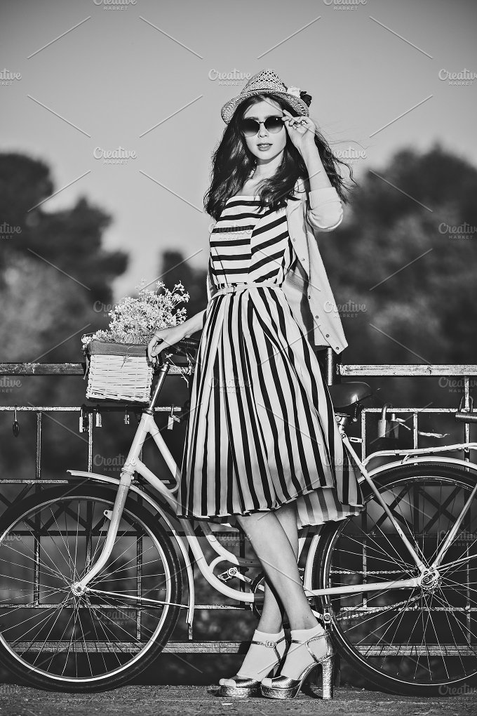 Young beautiful, elegantly dressed woman with bicycle. Beauty fashion and lifestyle - People