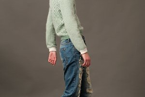 fashion model pose in blue jeans and woolly sweater