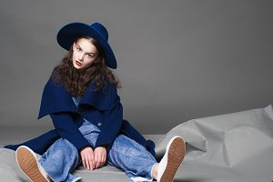 fashion model woman coat and hat urban style pose on color background in studio