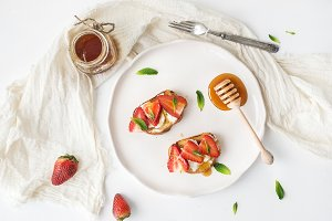 French toasts with strawberry, cream cheese, honey and mint on light ceramic plate