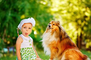 Little girl and dog sheltie.