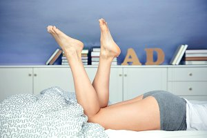 Closeup of beautiful woman legs lying on bed