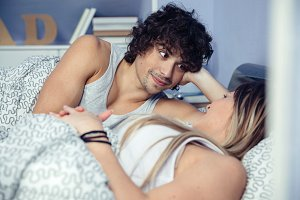 Man looking to beautiful woman lying on bed