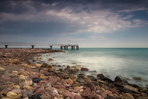 Pier in a pebbles beach