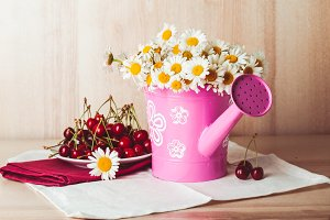 Flower pot and a plate of cherries