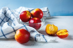 Five ripe nectarines on blue