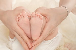 Mother holds feet of her daughter.