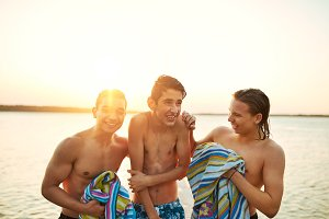 Three young teenage boys after swimming in a lake